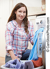 Portrait Of Woman Doing Laundry At Home
