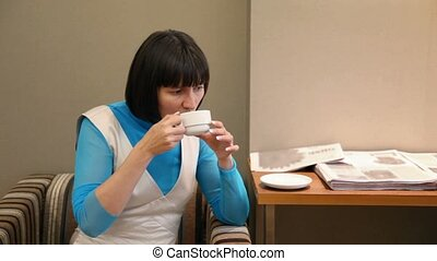 portrait of woman drinking tea  sitting in armchair