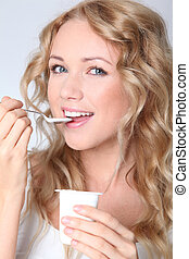 Portrait of woman eating yogurt