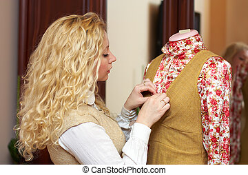 Portrait of woman, fashion designer, dressmaker working with tailoring mannequin at home studio
