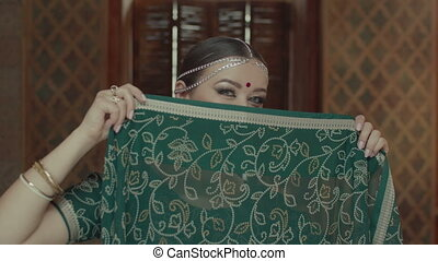 Portrait of woman flirting, covering face with sari -...
