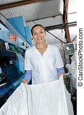 Portrait of woman folding laundry