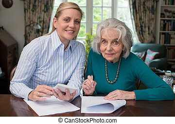 Portrait Of Woman Helping Senior Neighbor With Paperwork