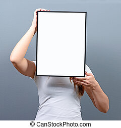 Portrait of woman hiding behind blank sign board