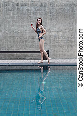 portrait of woman holding a glass in swimming pool