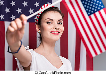 portrait of woman holding american flag in hand and looking at camera, Independence Day concept