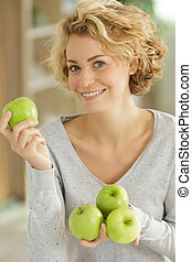 portrait of woman holding apples