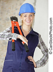 portrait of woman holding bolt croppers on her shoulder