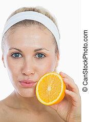 Portrait of woman holding orange slice