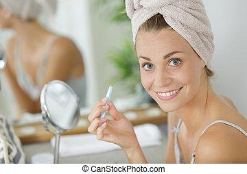 portrait of woman holding tweezers