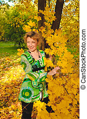 Portrait of woman in autumn leaves