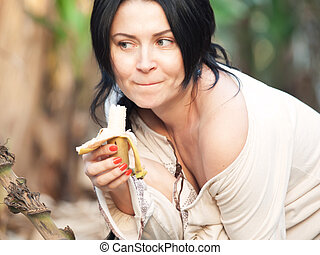Portrait of woman in beige blouse with banana with sense of humor, against of banana trees