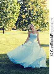 woman in blue tulle dress dancing in the park