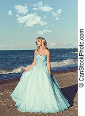 woman in blue tulle dress enjoying sun on beach