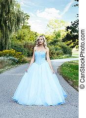 woman in blue tulle dress on garden path