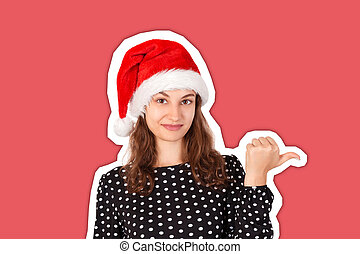 portrait of woman in dress pointing left with thumb and confused. emotional girl in santa claus christmas hat isolated on white background. holiday concept