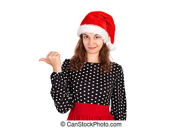 portrait of woman in dress pointing left with thumb and upset. emotional girl in santa claus christmas hat isolated on white background. holiday concept