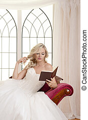 woman in evening dress reading a book and playing with her hair