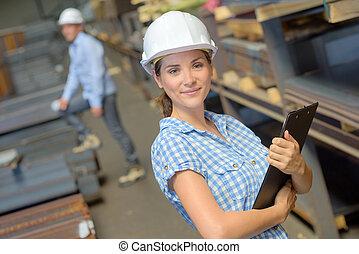 Portrait of woman in hardhat holding clipboard