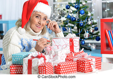 Portrait of woman in Santa hat with presents