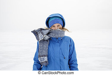 Portrait of woman in scarf and blue warm jacket standing alone on the lake ice. Cold cloudy winter day