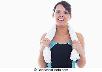 Portrait of woman in sportswear holding towel around neck