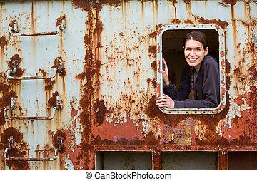 Portrait of woman in the window of an abandoned iron rusty waggon.