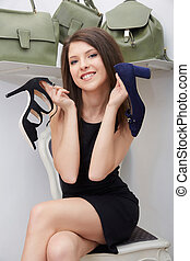 portrait of woman keeping high heeled shoe in shopping center