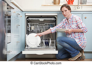 Portrait Of Woman Loading Dishwashwasher In Kitchen