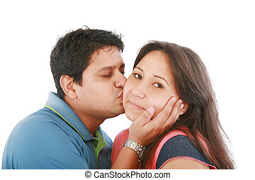 Portrait of woman looking at camera with man near by kissing her