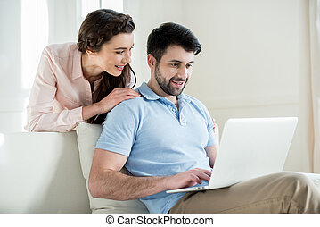portrait of woman looking at man using laptop at home