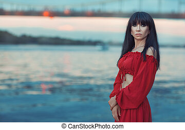 Portrait of woman on a river bank at sunset.