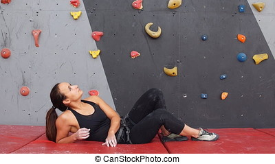 Portrait of woman on artificial exercise climbing wall. -...