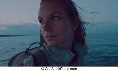 Portrait of woman on deck of boat at sunset - Closeup...