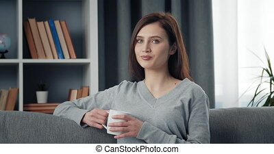 Portrait of woman relaxing at home with cup of coffee