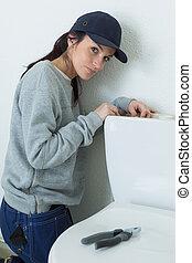 Portrait of woman repairing toilet cistern