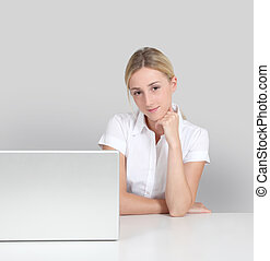 Portrait of woman sitting by laptop computer