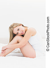Portrait of woman sitting in bed