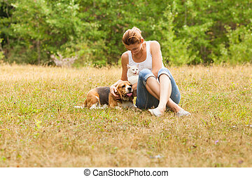 Portrait of woman sitting on grass near her dog and cat