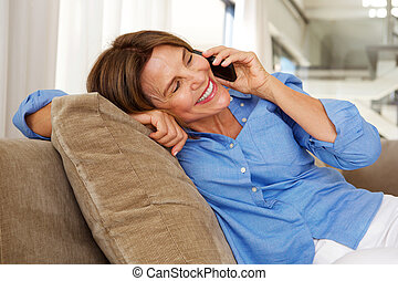 woman sitting on sofa at home with mobile phone