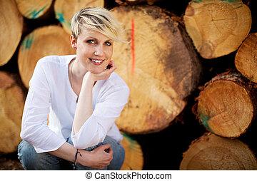 Portrait Of Woman Smiling Against Logs
