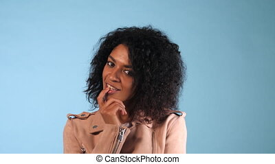 Portrait of woman smiling to camera, flirting, winds hair on finger and seductively bites her lip. Beautiful young mixed race trendy girl with afro hairstyle.