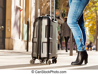 Portrait of woman standing on street with suitcase