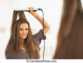 Portrait of woman straightening hair with straightener