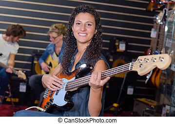 Portrait of woman strumming guitar