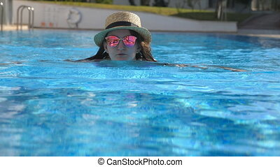 Portrait of woman swimming in pool in sunglasses and hat during summer vacation. Young beautiful girl relaxing in basin. Holiday concept. Close up Slow motion