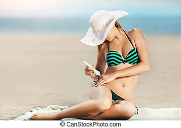 Portrait of woman taking skincare with sunscreen lotion at...