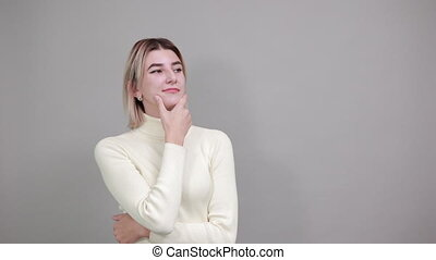 Portrait of young woman in pastel white shirt thinking gesture, looking aside, keeping hand on chin over isolated white wall background. People sincere emotions, lifestyle concept