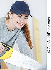 Portrait of woman using handsaw
