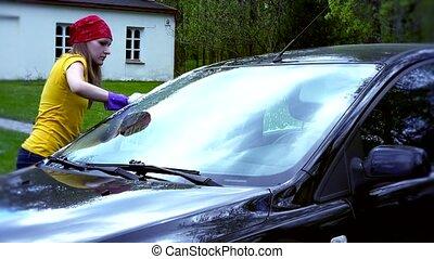 Portrait Of Woman Washing Car in house yard.